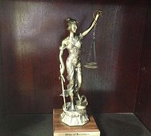 An imagine of a trophy awarded to a new member of the Order of the Barristers.  The trophy consists of a statute of Lady Justice.