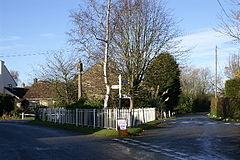 Street scene with area between two roads containing trees and stone column behind a white fence.