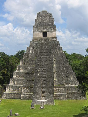 a steep-sided, stepped pyramid with a central staircase that rises from a flat, grassy area to a temple doorway at the top