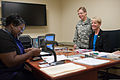 Tracey Hepner, seated at right, the spouse of U.S. Army Brig. Gen. Tammy Smith, standing, waits to receive her military dependent identification card at the U.S. Army Reserve headquarters at Fort Bragg, N.C 130903-A-XN107-180.jpg