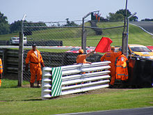 a group of people in fluorescent boilersuits stand behind a barrier, with one of them waving a red flag over the top of the barrier