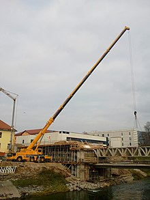 Truck-mounted crane building a bridge.jpg