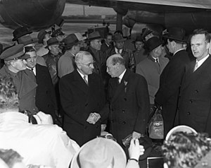 Truman and Attlee in dark suits shake hands. There are surrounded by a crowd of people, all dressed warmly. In the background is a propeller driven airliner.