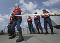 U.S. Navy Electronics Technician 2nd Class Timothy Miller, foreground left, assigned to the guided missile destroyer USS Mason (DDG 87), heaves in a line during a replenishment in the Arabian Sea Oct. 1, 2013 131001-N-PW661-011.jpg