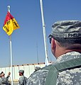 """US Army 52516 Col. Larry Phelps, 15th Sustainment Brigade commander, watches as Soldiers raise the """"Wagonmaster"""" flag in front of the brigade's headquarters here Oct. 5 after a transfer of authority ceremony. (U.S.jpg"""