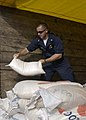 US Navy 050120-N-4211M-008 A Chief Petty Officer helps move rice for the refugees around the area during the humanitarian operation on the privilege of helping the people of Tsunami devastated region of Aceh Sumatra.jpg