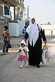 US Navy 071216-M-4804L-016 An Iraqi woman smiles as she walks with her daughter.jpg