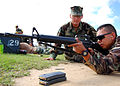 US Navy 090518-N-1120L-007 Religious Program Specialist 2nd Class Michael Pornovets, a range coach for Naval Mobile Construction Battalion (NMCB) 7, watches Storekeeper 2nd Class Shawn Apgar as he sights in his M16A2 service ri.jpg