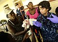 US Navy 100125-N-5345W-094 Hospital Corpsman 1st Class Vilma Bauer, assigned to the amphibious dock landing ship USS Fort McHenry (LSD 43) examines a Haitian infant as her family looks on.jpg