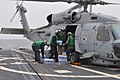 US Navy 110315-N-9930Q-025 Sailors assigned to Helicopter Anti-Submarine Squadron Light (HSL) 43 load cases of bottled water on an SH-60 Sea Hawk h.jpg