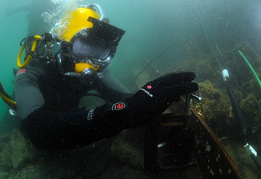 US Navy 110804-N-XD935-310 Navy Diver 3rd Class Bryan Myers uses a clamp to secure a steel plate before conducting welding operations