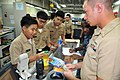 US Navy 110923-N-CB621-016 A Navy Junior ROTC cadet from Father Duenas Memorial School makes a purchase from Ship's Serviceman Seaman Mark Seward.jpg