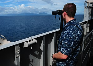 US Navy 120101-N-SK590-031 Engineman 2nd Class Angel Fix looks at the coastline of an island in the Philippines from the Nimitz-class aircraft carr.jpg