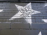 Graffitti con el nombre de la banda sobre una pared de ladrillo.