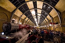 "On the left is a red steam locomotive and three carriages, with steam drifting out above.  On the right passengers queue behind barriers and signs that say ""Hogwarts Express"" and ""Platform 9¾"".  Over both of these is a large cylindrical glass and steel roof."