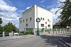 Vue d'une maison particulière de taille importante, cubique et ajouré de quelques fenêtres jaunes. La rue et une horloge publique sont au premier plan.