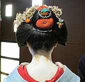 A maiko wearing a blue kimono viewed from the back.