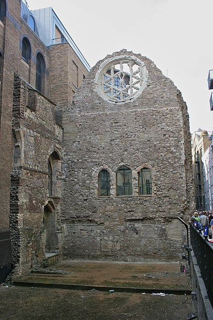 Remains of the great hall of Winchester Palace, yards from London Bridge in Southwark showing the Rose Window and underneath the traditional arrangement of three doors from the screens passage to the buttery, pantry and kitchen. Winchester Palace.jpg