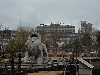 Qixia District - A bixie (winged lion) at the tomb of Xiao Hui, seen against the background of Ganjiaxiang, an industrial section of Qixia District