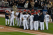 Several men in pinstriped pants and red baseball caps, some wearing pinstriped baseball jerseys and some dark blue-hooded sweatshirts, stand in a group.