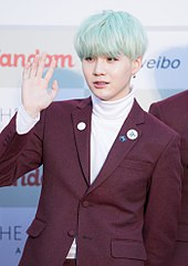 Suga, with blue hair and in a pink suit, holds his right hand up and looks left