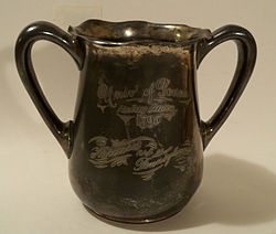 "A tarnished, metal, double-handled cup. An inscription, in script, reads: ""Univ of Penna/Relay Races/1895/Harvard vs. Pennsylvania."""