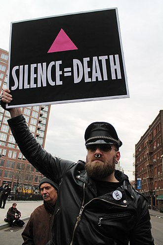 """HIV/AIDS activism - A demonstrator waves a placard using the """"Silence=Death"""" slogan during a 2017 event in New York City"""