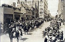 Сотни людей на лошадях маршируют по городской улице, наблюдая за людьми с тротуаров и крыш.