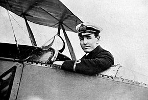A man in military uniform with peaked cap, sitting in the cockpit of a biplane