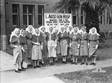 A group of nurses stand in front of a brick building
