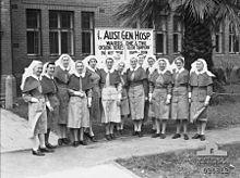Eine Gruppe von Krankenschwestern steht vor einem Backsteingebaude