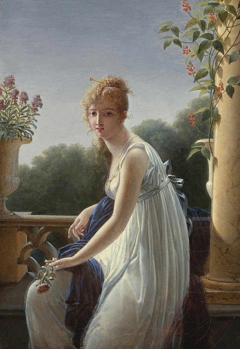 Una mujer joven sentada junto a una ventana.jpg