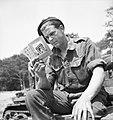 A soldier from 101st Light Anti-Aircraft Regiment prepares for D-Day by reading his French handbook at a camp near Portsmouth, 29 May 1944. H38831.jpg