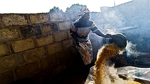Parboiled rice - Woman preparing parboiled rice in Nigeria