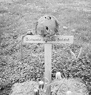 Wooden cross on grave with a steel helmet on top of cross