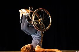 A woman in dark, close-fitting clothes and a wheelchair lies on her back, stabilizing herself with her arms and lifting her legs, along with the wheelchair, over her head