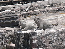 Deux crapauds stylisés, sculptés dans de la pierre grise