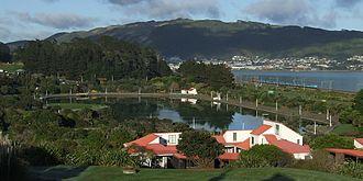 Porirua - Police College chalets above the Aotea Lagoon, with Colonial Knob on the skyline above the city centre (obscured) and Elsdon and Takapuwahia