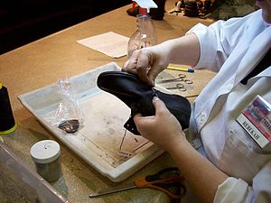 Arabia Steamboat Museum - Preservationist restitching a shoe in the Arabia Steamboat Museum's preservation lab