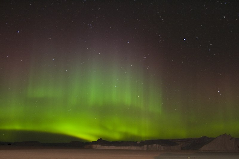 A swirling green glow in the night sky above snow-covered ground