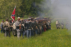 reenactors fire their rifles during a reenactment of the Battle