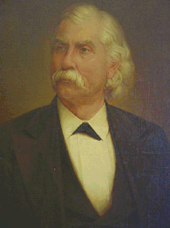 Upper body of a well-dressed man with a white mustache and white hair