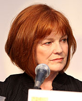 A color headshot of Blair Brown at a microphone