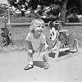 Blond kindje met Mickey Mouse hobbelpaard in Suriname, Bestanddeelnr 252-6863.jpg