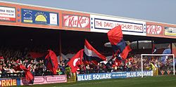 One of the stands of the Bootham Crescent association football ground, with supporters waving flags