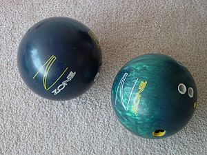 Bowling ball - Two reactive resin bowling balls. Both are the same model, but one is pearlized (right) and one is not (left).