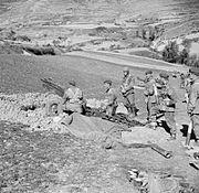 Six men around an artillery gun dug in with another gun in the distance