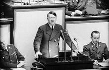 Photo noir et blanc prise le 4 mai 1941, à l'intérieur du Reichstag. Au centre de la photo, Adolf Hitler, debout, mains appuyées de part et d'autre d'un pupitre noir supportant 4 micros, prononce un discours. Il porte une cravate noire, une chemise blanche et une veste croisée sombre. Deux officiers sont assis à ses côtés. L'arrière-plan est constitué de trois panneaux de couleur claire.