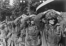 Eight men walking towards the camera with the hands on their heads