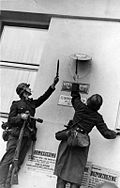 Wehrmacht soldiers destroying Polish government insignia